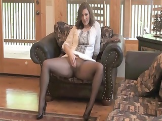 Brunette MILF sits on her chair in nylons and